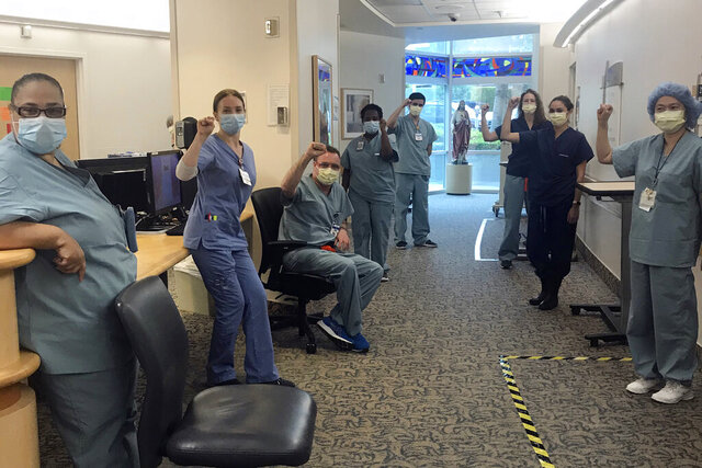 In this image provided by Lizabeth Baker Wade, nurses at Providence Saint John's Health Center in Santa Monica, Calif., on April 10, 2020, raise their fists in solidarity after telling managers they can't care for COVID-19 patients without N95 respirator masks to protect themselves. The hospital has suspended ten nurses from the ward, but has started providing nurses caring for COVID-19 patients with N95 masks. (Lizabeth Baker Wade via AP)