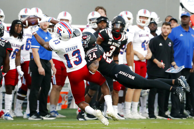 Louisiana Tech's Isaiah Graham (13) hauls in a pass over North Carolina State's Derrek Pitts Jr. (24) during the first half of an NCAA college football game in Raleigh, N.C., Saturday, Oct. 2, 2021. (AP Photo/Karl B DeBlaker)