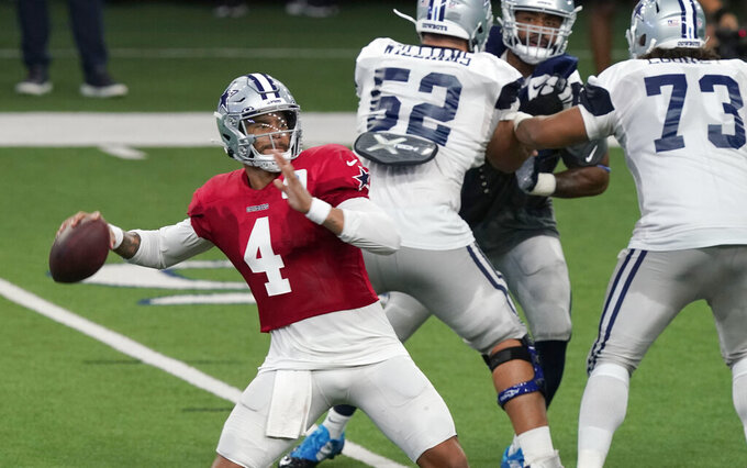 Dallas Cowboys quarterback Dak Prescott (4) passes with blocking by Connor Williams (52) and Joe Looney (73) during an NFL football training camp in Frisco, Texas, Monday, Aug. 24, 2020. (AP Photo/LM Otero)