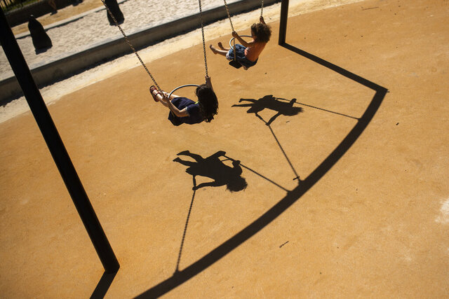 FILE - In this Thursday, May 28, 2020 file photo, children swing in a playground at Leopold park during the partial lifting of coronavirus, COVID-19, lockdown regulations in Brussels. The European Union's external auditor said Tuesday, Sept. 29, 2020 that child poverty has reached worrying levels across the world's largest economy, and has become an unacceptable situation likely to worsen during the coronavirus pandemic. (AP Photo/Francisco Seco, File)