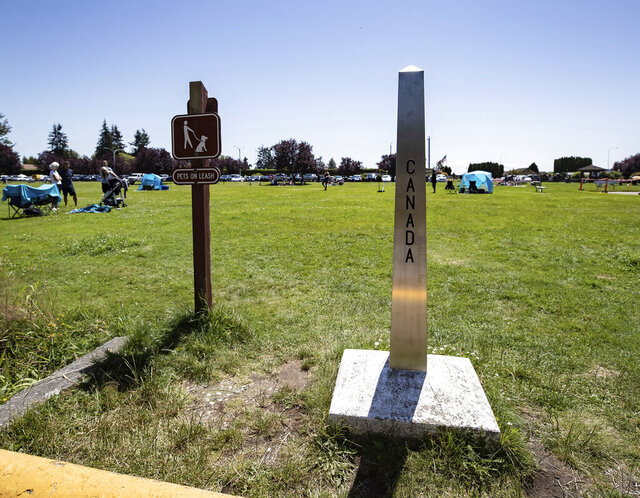 A Canada-U.S. border marker stands in Surrey, British Columbia, as people gather at Peace Arch Historical State Park in Blaine, Wash., Sunday, July 5, 2020. Although the B.C. government closed the Canadian side of the park in June due to concerns about crowding and COVID-19, people are still able to meet in the U.S. park due to a treaty signed in 1814 that allows citizens of Canada and the U.S. to unite in the park without technically crossing any border. (Darryl Dyck/The Canadian Press via AP)