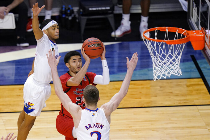 Eastern Washington guard Michael Meadows (25) goes up for a shot at Kansas guard Dajuan Harris, left, and teammate Christian Braun (2) defend during the second half of a first-round game in the NCAA college basketball tournament at Farmers Coliseum in Indianapolis, Saturday, March 20, 2021. (AP Photo/AJ Mast)