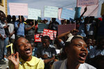 A theater troupe of university students perform as grade school students reciting a lesson on Haiti's constitution and government, during a protest calling for President Jovenel Moïse to resign so that schools can reopen, in Port-au-Prince, Haiti, Monday, Oct. 21, 2019. Many schools around the country have now been closed for more than a month as protests block roads and paralyze the economy. The United Nations said in early October that roughly 2 million children were unable to go to school due to the unrest. (AP Photo/Rebecca Blackwell)