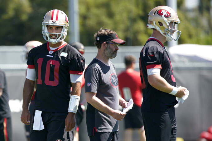 San Francisco 49ers quarterback Jimmy Garoppolo (10) and quarterback C.J. Beathard, right, watch during drills at the team's NFL football training facility in Santa Clara, Calif., Tuesday, June 11, 2019. (AP Photo/Tony Avelar)