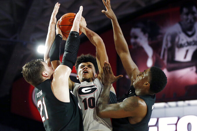 Georgia's Toumani Camara (10) is stoped by South Carolina forwards Maik Kotsar (21) and Keyshawn Bryant during an NCAA college basketball game Wednesday, Feb. 12, 2020, in Athens, Ga. (Joshua L. Jones/Athens Banner-Herald via AP)