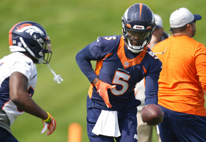 Denver Broncos quarterback Teddy Bridgewater, right, hands off the ball to running back Javonte Williams as they take part in drills during an NFL football training camp at the team's headquarters Tuesday, Aug. 10, 2021, in Englewood, Colo. (AP Photo/David Zalubowski)