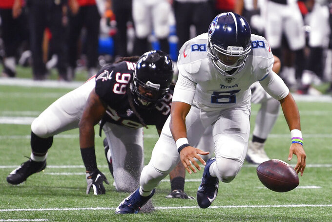 Tennessee Titans quarterback Marcus Mariota (8) works to recover his fumble against the Atlanta Falcons during the second half of an NFL football game, Sunday, Sept. 29, 2019, in Atlanta. (AP Photo/John Amis)