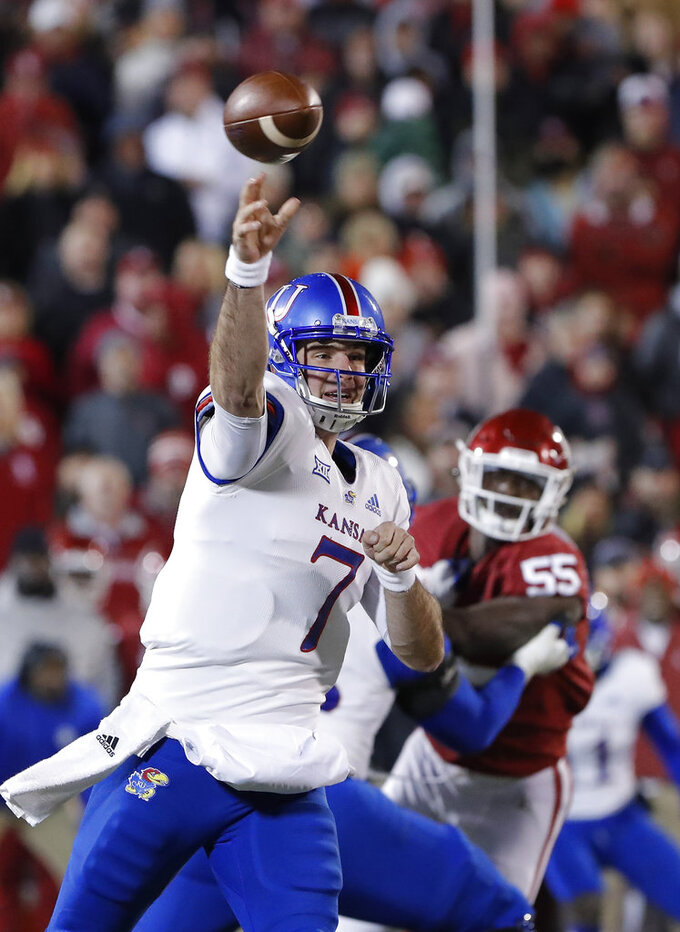 Kansas quarterback Peyton Bender (7) passes against Oklahoma during the first half of an NCAA college football game in Norman, Okla., Saturday, Nov. 17, 2018. (AP Photo/Alonzo Adams)