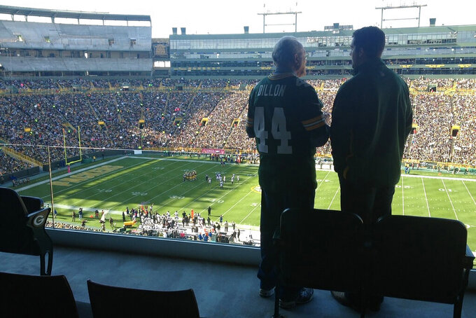 In this October 2012 photo provided by Karen Gooch, former Green Bay Packers football player Bobby Dillon and his grandson, Weston Gooch are shown in a suite at Lambeau Field in Green Bay, Wisc. He left with an outstanding resume, but also with the ugly remnants of a series of concussions from playing football. Of the 26 men who entered the Pro Football Hall of Fame as Packers and preceded Bobby Dillon into the shrine, nearly all won an NFL championship in Green Bay. Dillon never got the chance. (Karen Gooch via AP)