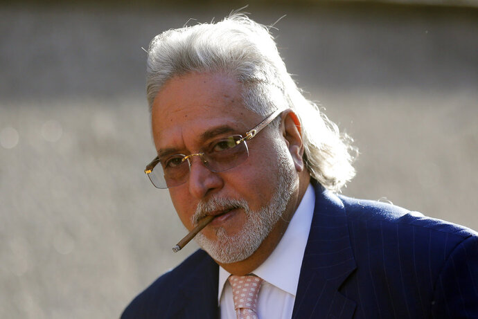 """FILE- In this Dec. 14, 2017 file photo, F1 Force India team boss Vijay Mallya arrives at Westminster Magistrates Court in London. A New Delhi court has declared India's flamboyant tycoon Vijay Mallya a """"proclaimed offender"""" for failing to appear to answer allegations of money laundering by flouting foreign currency laws. Thursday's order paves the way for the government to take over Mallya's businesses and real estate holdings. (AP Photo/Frank Augstein, File)"""