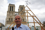 General Jean-Louis Georgelin who is to oversee reconstruction of Notre Dame Cathedral, attends an interview after carpenters put the skills of their Medieval colleagues on show on the plaza in front of Notre Dame Cathedral in Paris, France, Saturday, Sept. 19, 2020, the day honoring European heritage, by reproducing for the public a section of the elaborate carpentry used when the edifice was built. The elaborate wooden beams went up in flames in a devastating April 2019 fire that also toppled the spire of the cathedral, now being renovated. (AP Photo/Francois Mori)