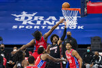 Miami Heat's Gabe Vincent, center right, goes up for the shot against Philadelphia 76ers' Joel Embiid, center left, and Tyrese Maxey, left, during the first half of an NBA basketball game, Thursday, Jan. 14, 2021, in Philadelphia. (AP Photo/Chris Szagola)