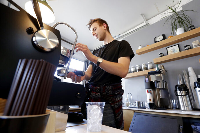 In this Monday, Nov. 4, 2019, photo, barista Porter Hahn makes an iced coffee drink for a customer in a coffee shop in Seattle. On Tuesday, Nov. 5, the Institute for Supply Management, a trade group of purchasing managers, issues its index of non-manufacturing activity for September. (AP Photo/Elaine Thompson)