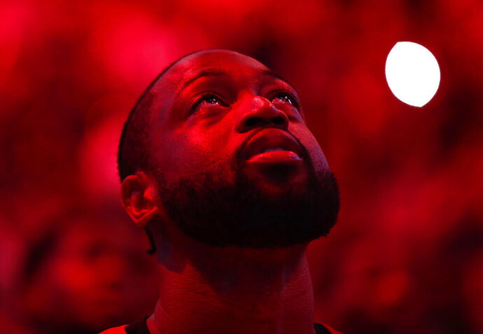 Miami Heat guard Dwyane Wade stands during a ceremony in his honor as he is playing his final home regular season game when the Heat host the Philadelphia 76ers, Tuesday, April 9, 2019, in Miami. Wade is retiring at the end of the season. (AP Photo/Brynn Anderson)