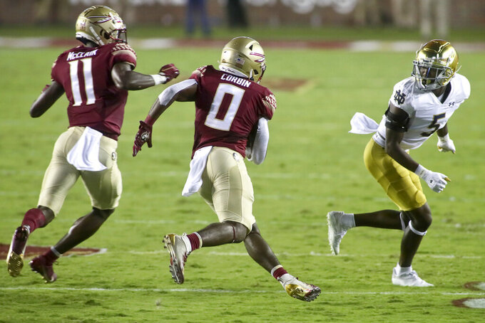 Notre Dame cornerback Cam Hart (5), right, watches as Florida State running back Jashaun Corbin (0) makes a cut en route to a long touchdown in the first quarter of an NCAA college football game Sunday, Sept. 5, 2021, in Tallahassee, Fla. (AP Photo/Phil Sears)