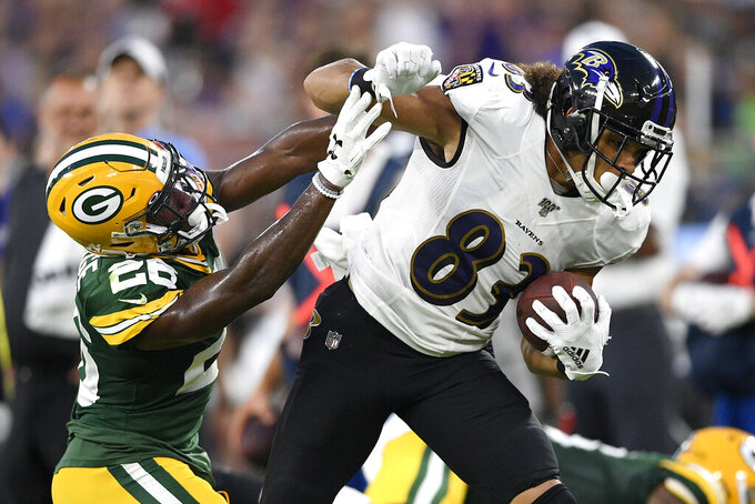 Baltimore Ravens wide receiver Willie Snead, right, runs with the ball as Green Bay Packers defensive back Darnell Savage (26) tries to stop him during the first half of a NFL football preseason game, Thursday, Aug. 15, 2019, in Baltimore. (AP Photo/Nick Wass)