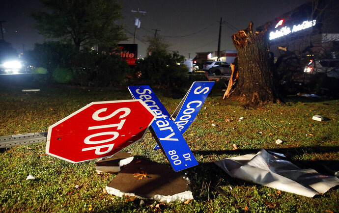 The street sign on Cooper St. at Secretary Dr. was blown over in Arlington when a tornado-warned storm blew through, Tuesday night, Nov. 25, 2020. No one was seriously injured across the street at the Burger Box restaurant. (Tom Fox/The Dallas Morning News via AP)