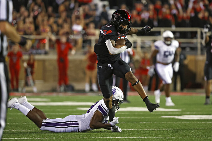 Texas Tech's Erik Ezukanma (13) breaks a tackle attempt by Stephen F. Austin's Bruce Harmon (23) during the second half of an NCAA college football game Saturday, Sept. 11, 2021, in Lubbock, Texas. (AP Photo/Brad Tollefson)