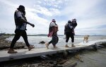 Haitian migrants walk on the dock to a boat that will take them to Acandi, near the border with Panama, as they depart Necocli, Colombia, Monday, Sept. 13, 2021. Migrants have been gathering in Necocli as they move north on their way to the U.S. border. (AP Photo/Fernando Vergara)