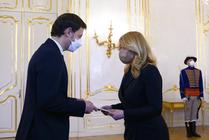 Slovakia's President Zuzana Caputova, right, tasks Vice-premier  Eduard Heger with forming a new government at the Presidential Palace in Bratislava, Slovakia, on Tuesday, March 30, 2021.  Slovakia's prime minister and his government resigned to end the political crisis triggered by a secret deal to buy Russia's Sputnik V coronavirus vaccine.(Pavel Neubauer/TASR via AP)