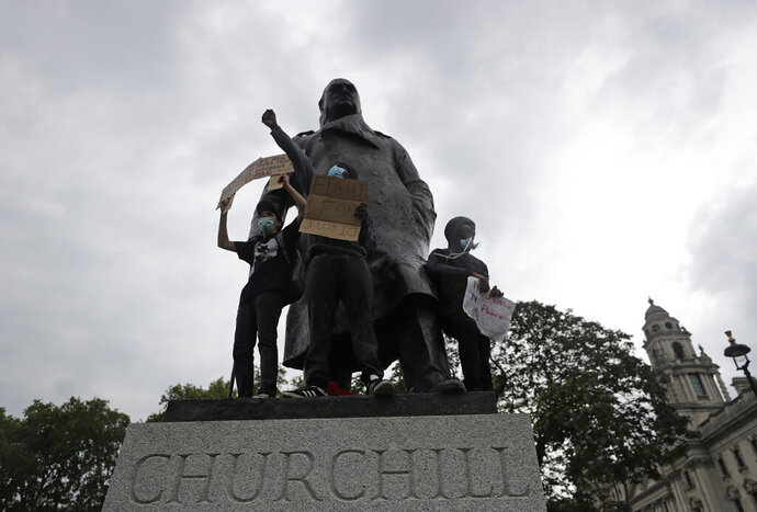 Protesters stand on the statue of former British Prime Minister Winston Churchill during a demonstration in Parliament Square in London on Wednesday, June 3, 2020, over the death of George Floyd, a black man who died after being restrained by Minneapolis police officers on May 25. Protests have taken place across America and internationally, after a white Minneapolis police officer pressed his knee against Floyd's neck while the handcuffed black man called out that he couldn't breathe. The officer, Derek Chauvin, has been fired and charged with murder. (AP Photo/Kirsty Wigglesworth)