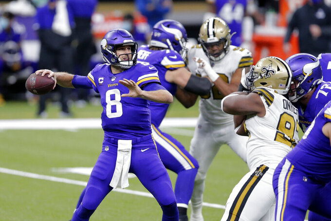 Minnesota Vikings quarterback Kirk Cousins (8) passes under pressure from New Orleans Saints defensive tackle David Onyemata in the first half of an NFL football game in New Orleans, Friday, Dec. 25, 2020. (AP Photo/Brett Duke)