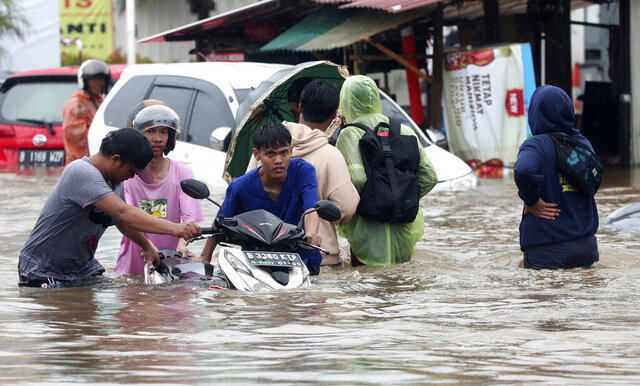Indonesian people wade through floodwaters at Jatibening on the outskirt of Jakarta, Indonesia, Wednesday, Jan. 1, 2020. Severe flooding hit Indonesia's capital just after residents celebrating New Year's Eve, forcing a closure of an airport and thousands of inhabitants to flee their flooded homes. (AP Photo/Achmad Ibrahim)