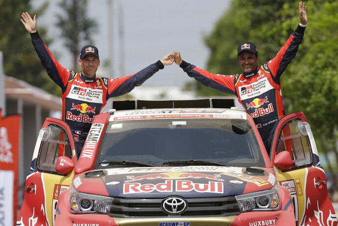 Toyota driver Nasser Al-Attiyah, of Qatar, and co-driver Matthieu Baumel of France, wave during the Dakar Rally ceremonial start in Lima, Peru, Saturday, Jan. 6, 2018. The 40th edition of the Dakar Rally, the tenth to be held in South America, will start in Lima on Jan. 6 to run south along the Pacific coast and cross Bolivia to finish in Cordoba, Argentina on Jan. 20. (AP Photo/Martin Mejia)