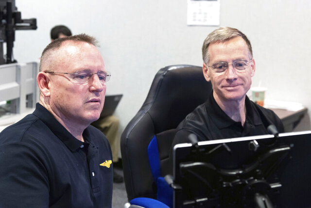 In this Nov. 29, 2018 photo made available by NASA, Commercial Crew Program & Boeing Crew Flight Test astronauts Butch Wilmore, left, and Chris Ferguson participate in a flight control simulation for a Boeing CST-100 Starliner capsule at the Johnson Space Center in Houston. On Wednesday, Oct. 7, 2020, Ferguson removed himself from the first Starliner crew, citing his daughter's wedding in 2021. He has been replaced on the crew by Wilmore. (James Blair/NASA via AP)