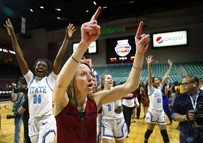 New Mexico State head coach Brooke Atkinson celebrates with the team after New Mexico State beat Texas-Rio Grande Valley 76-73 in double overtime during a NCAA college basketball Western Athletic Conference Women's Tournament championship game Saturday, March 16, 2019, in Las Vegas. (AP Photo/Steve Marcus)