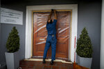 A worker builds a see-through barrier that will have sleeves for hugging at the Reminiscencias residence for the elderly in Tandil, Argentina, Monday, April 5, 2021. Residents here do not have physical contact with their families or leave the residence due to the COVID-19 pandemic, but stay active with group activities within the facility. (AP Photo/Natacha Pisarenko)