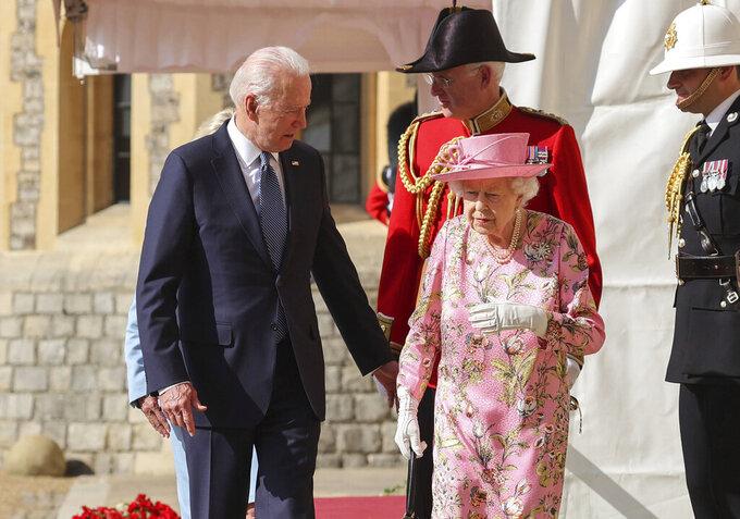 Britain's Queen Elizabeth II, right, walks with US President Joe Biden during his visit to Windsor Castle, near London, Sunday June 13, 2021. (Chris Jackson/Pool Photo via AP)