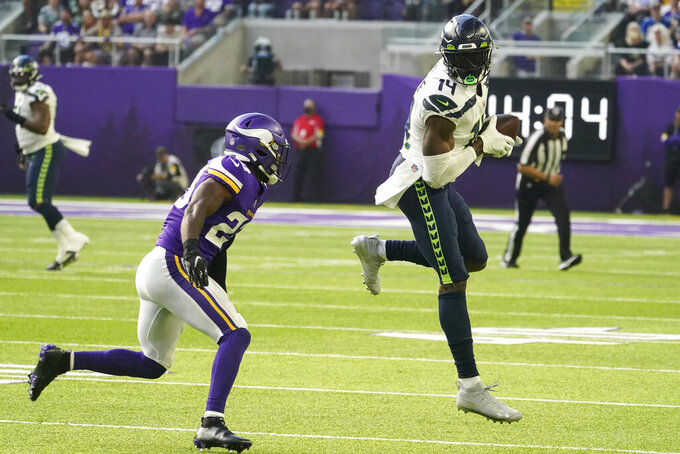 Seattle Seahawks wide receiver DK Metcalf (14) makes a catch in front of Minnesota Vikings free safety Xavier Woods (23) in the first half of an NFL football game in Minneapolis, Sunday, Sept. 26, 2021. (AP Photo/Jim Mone)