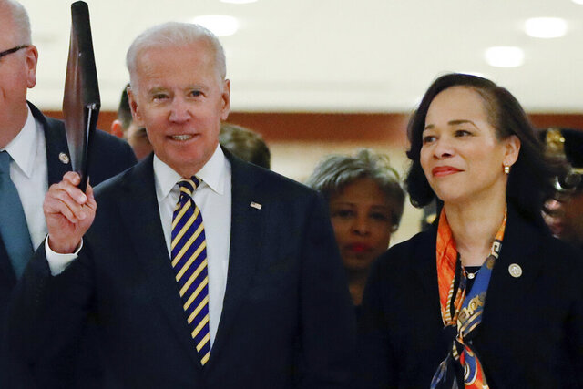 FILE - In this Feb. 7, 2018 file photo, Democratic presidential candidate former Vice President Joe Biden, center, escorted by RRep. Lisa Blunt Rochester, D-Del., right, as they arrive at the House Democratic Issues Conference on Capitol Hill in Washington. The 2020 vice presidential search now rests with Democratic presidential candidate Joe Biden as he prepares to pick just the third woman in history for a major U.S. party's national ticket. There's a group of key advisers who have helped shape his options and present him with reams of pros and cons for potential vice presidents. They include Delaware Rep. Lisa Blunt Rochester, former Connecticut Sen. Chris Dodd, Los Angeles Mayor Eric Garcetti and former Apple executive and longtime Biden adviser Cynthia Hogan. They're aided by lawyers with deep ties to Democratic politics and former President Barack Obama.(AP Photo/Pablo Martinez Monsivais)