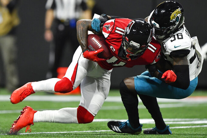 Atlanta Falcons wide receiver Julio Jones (11) is hit by Jacksonville Jaguars safety Ronnie Harrison (36) during the first half of an NFL football game, Sunday, Dec. 22, 2019, in Atlanta. (AP Photo/John Amis)