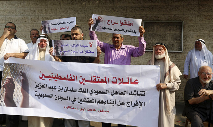 Families of Palestinians held in jails in Saudi Arabia, hold placards in Arabic that some read,