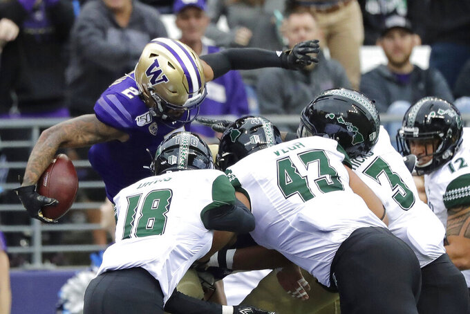 Washington wide receiver Aaron Fuller leaps over Hawaii's Cortez Davis (18), Mason Vega (43) and Kalen Hicks (3) during the first half of an NCAA college football game, Saturday, Sept. 14, 2019, in Seattle. (AP Photo/Ted S. Warren)