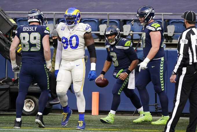 Seattle Seahawks quarterback Russell Wilson (3) reacts after running for a touchdown against the Los Angeles Rams during the second half of an NFL football game, Sunday, Dec. 27, 2020, in Seattle. (AP Photo/Elaine Thompson)