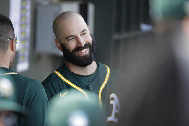 Oakland Athletics' Mike Fiers smiles in the dugout during the second inning of a spring training baseball game against the San Francisco Giants, Sunday, Feb. 23, 2020, in Mesa, Ariz. (AP Photo/Darron Cummings)