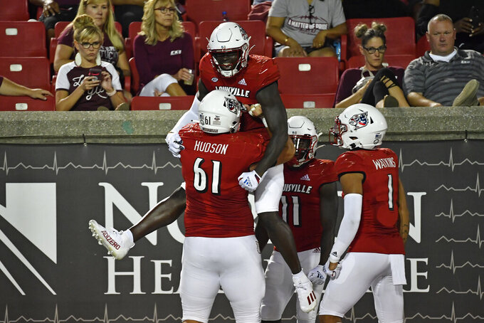 Louisville defensive back Benjamin Perry (10) is held up by offensive lineman Bryan Hudson (61 following his touchdown against Eastern Kentucky during the second half of an NCAA college football game in Louisville, Ky., Saturday, Sept. 11, 2021. (AP Photo/Timothy D. Easley)
