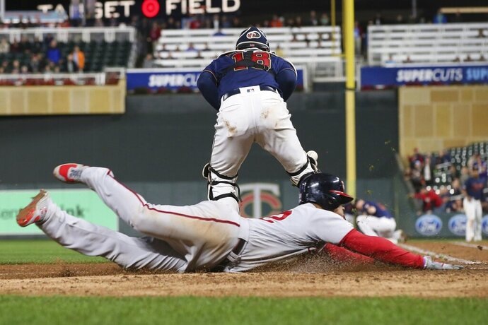 Washington Nationals' left fielder Juan Soto, right, scores on a triple by Asdrubal Cabrera as Minnesota Twins' catcher Mitch Garver chases the ball in the fifth inning of a baseball game Thursday, Sept. 12, 2019, in Minneapolis. (AP Photo/Jim Mone)