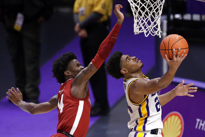 LSU guard Cameron Thomas (24) goes to the basket as Alabama guard Keon Ellis (14) defends during the second half of an NCAA college basketball game in Baton Rouge, La., Tuesday, Jan. 19, 2021. (AP Photo/Brett Duke)