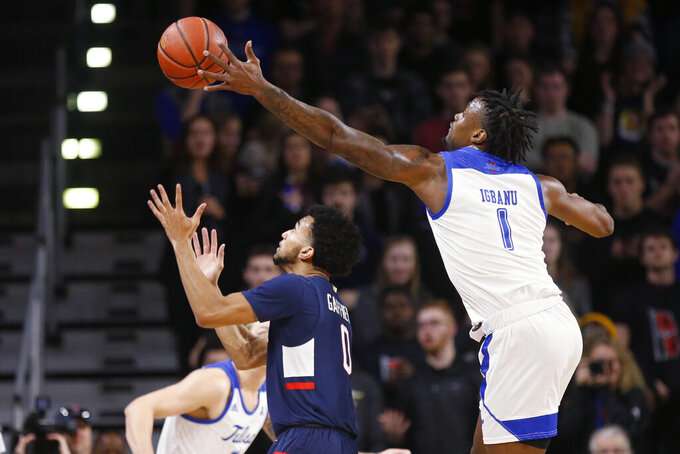 Tulsa forward Martins Igbanu (1) reaches for the ball over Connecticut guard Jalen Gaffney (0) during the first half of an NCAA college basketball game in Tulsa, Okla., Thursday, Feb. 6, 2020. (AP Photo/Sue Ogrocki)