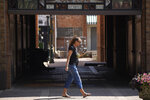 In this Friday, July 223, 2021, photograph, a pedestrian looks at a mobile device while walking down a downtown sidewalk in Greeley, Colo.  Figures released this month show that population growth continues unabated in the South and West, even as temperatures rise and droughts become more common. That in turn has set off a scramble of growing intensity in places like Greeley to find water for the current population, let alone those expected to arrive in coming years. (AP Photo/David Zalubowski)