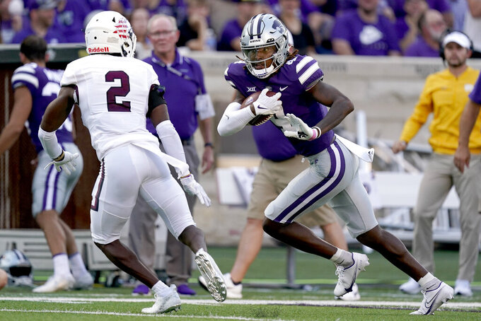 Kansas State wide receiver Malik Knowles (4) runs the ball under pressure from Southern Illinois cornerback James Ceasar (2) during the first half of an NCAA college football game, Saturday, Sept. 11, 2021, in Manhattan, Kan.(AP Photo/Charlie Riedel)