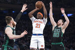 New York Knicks guard Damyean Dotson (21) shoots past Boston Celtics center Aron Baynes, left, and forward Gordon Hayward (20) during the first half of an NBA basketball game Friday, Feb. 1, 2019, at Madison Square Garden in New York. (AP Photo/Mary Altaffer)