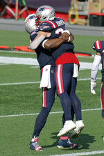New England Patriots quarterback Cam Newton, left, gives running back Rex Burkhead a lift after Burkhead's touchdown in the second half of an NFL football game against the Las Vegas Raiders, Sunday, Sept. 27, 2020, in Foxborough, Mass. (AP Photo/Steven Senne)