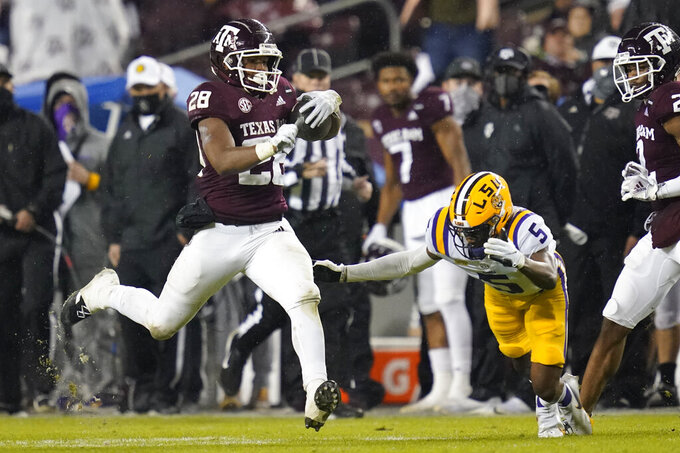 Texas A&M running back Isaiah Spiller (28) runs past LSU cornerback Jay Ward (5) for a first down during the first half of an NCAA college football game, Saturday, Nov. 28, 2020, in College Station, Texas. (AP Photo/Sam Craft)
