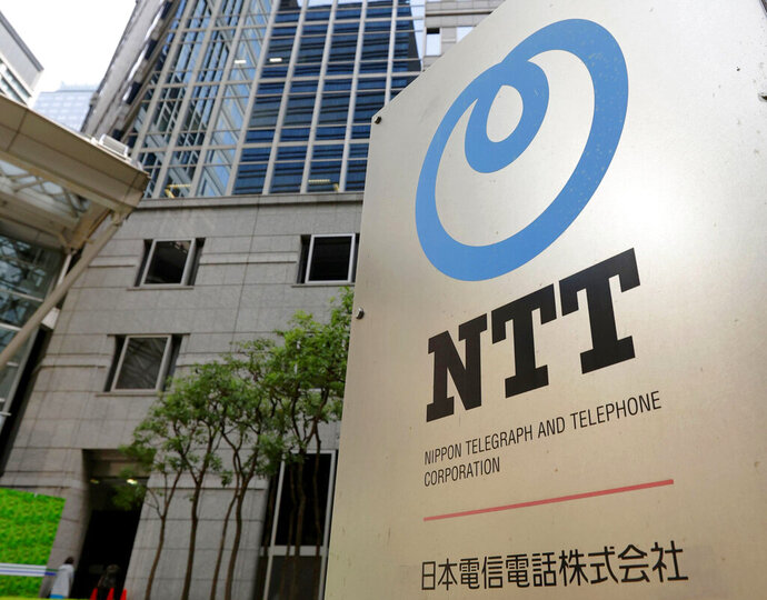 The corporate logo of  Japanese telecoms giant Nippon Telegraph & Telephone, or NTT, is seen in front of the building which houses its headquarters, in Tokyo, Tuesday, Sept. 29, 2020. Shares of NTT fell Tuesday on news it is preparing for a takeover of its mobile phone carrier NTT DoCoMo. (Kyodo News via AP)
