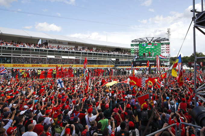Ferrari fans celebrate under the podium after Ferrari driver Charles Leclerc of Monaco won the Formula One Italy Grand Prix at the Monza racetrack, in Monza, Italy, Sunday, Sept.8, 2019. (AP Photo/Antonio Calanni)